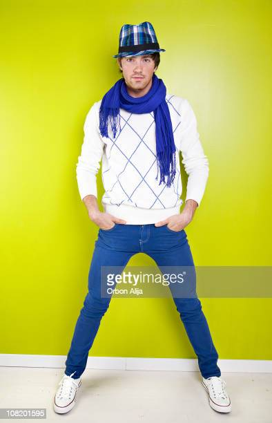 Trendy Young Man Wearing Jeans and Scarf Against Green Wall