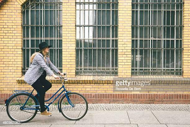 Trendige junge Frau mit Ihrem Fahrrad, urbane Landschaft im Hintergrund