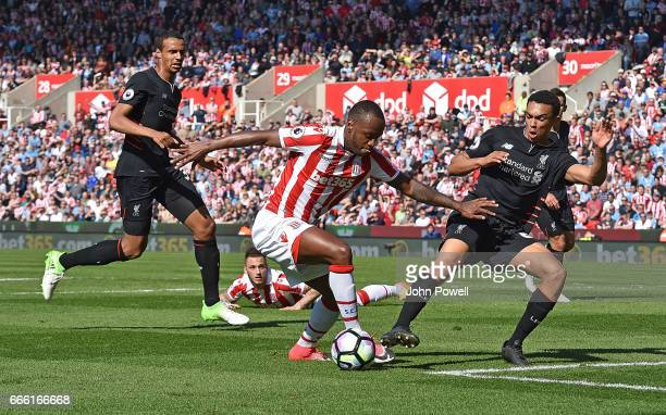 Trent AlexanderArnold of Liverpool with Saido Berahino of Stoke during the Premier League match between Stoke City and Liverpool at Bet365 Stadium on...
