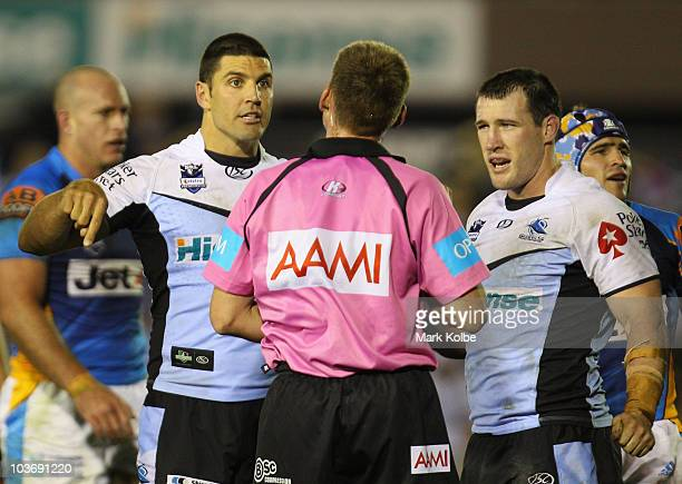 Trent Barrett and Paul Gallen of the Sharks discuss a decision with Referee Jason Robinson during the round 25 NRL match between the Cronulla Sharks...