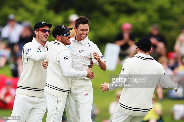 Trent Boult of New Zealand celebrates the wicket of Kumar Sangakkara of Sri Lanka with Hamish Rutherford and Brendon McCullum during day three of the...