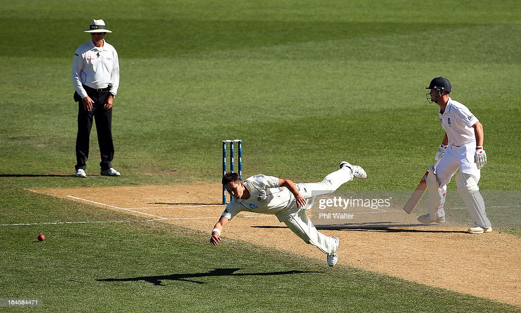 Trent Boult of New Zealand fields the ball as <a gi-track='captionPersonalityLinkClicked' href=/galleries/search?phrase=Jonathan+Trott&family=editorial&specificpeople=654505 ng-click='$event.stopPropagation()'>Jonathan Trott</a> of England looks on during day four of the Third Test match between New Zealand and England at Eden Park on March 25, 2013 in Auckland, New Zealand.