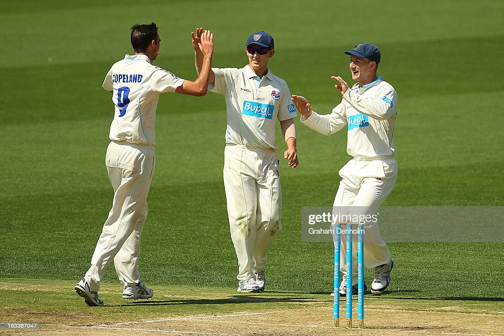 Trent Copeland, Nic Maddinson and Peter Nevill of the Blues celebrate the dismissal of William Sheridan of the Bushrangers during day three of the Sheffield Shield match between the Victorian Bushrangers and the New South Wales Blues at Melbourne Cricket Ground on March 9, 2013 in Melbourne, Australia.