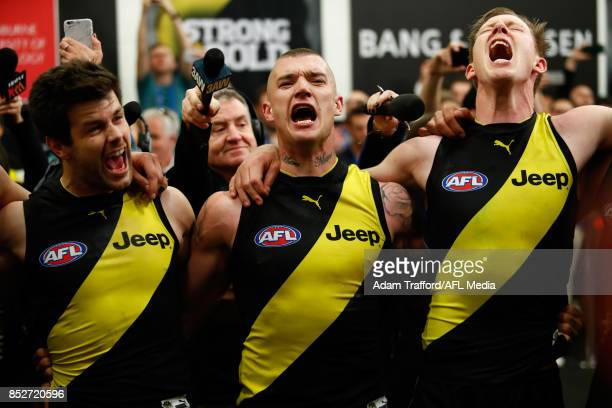 Trent Cotchin Dustin Martin and Jack Riewoldt of the Tigers sing the team song during the 2017 AFL Second Preliminary Final match between the...