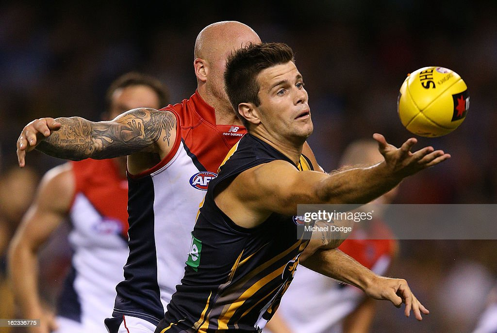 Trent Cotchin (R) of the Richmond Tigers reaches for the ball during the round one AFL NAB Cup match between the Richmond Tigers and the Melbourne Demons at Etihad Stadium on February 22, 2013 in Melbourne, Australia.