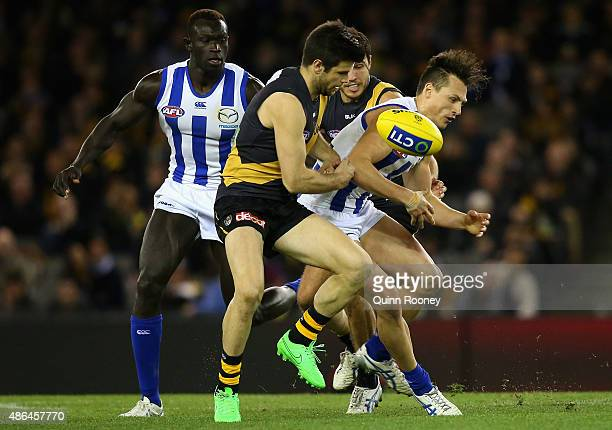 Trent Cotchin of the Tigers and Ben Jacobs of the Kangaroos compete for the ball during the round 23 AFL match between the Richmond Tigers and the...