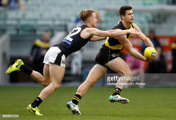 Trent Cotchin of the Tigers and Nick Graham of the Blues in action during the 2017 AFL round 14 match between the Richmond Tigers and the Carlton...