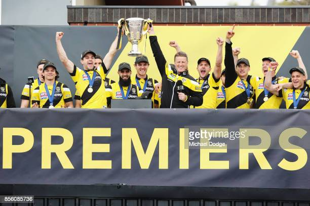 Trent Cotchin of the Tigers and Tigers head coach Damien Hardwick lift up the Premiership cup as players celebrate winning yesterday's AFL Grand...