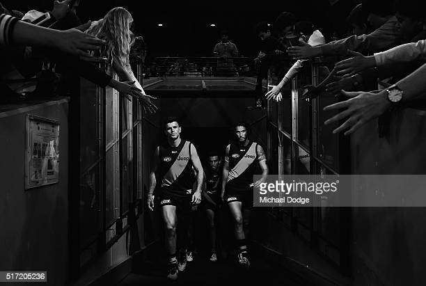 Trent Cotchin of the Tigers and Tyrone Vickery walk out during the round one AFL match between the Richmond Tigers and the Carlton Blues at Melbourne...