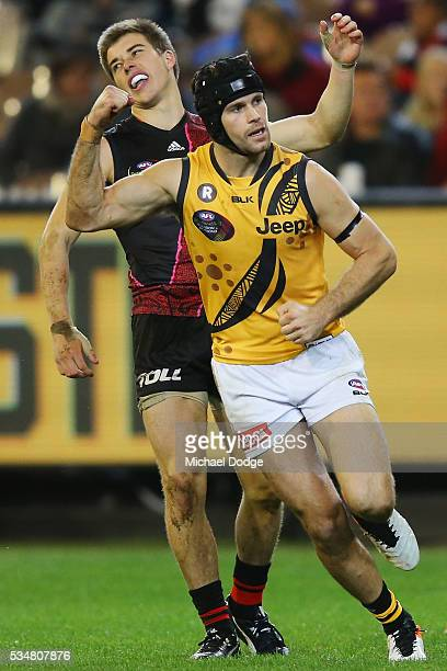 Trent Cotchin of the Tigers celebrates a goal ahead of Zach Merrett of the Bombers during the round 10 AFL match between the Essendon Bombers and the...