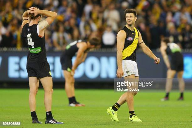 Trent Cotchin of the Tigers celebrates the win ext to Bryce Gibbs of the Blues during the round one AFL match between the Carlton Blues and the...