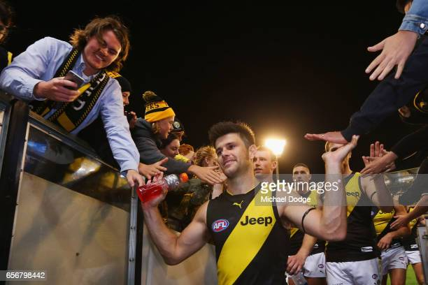 Trent Cotchin of the Tigers celebrates the win with fans during the round one AFL match between the Carlton Blues and the Richmond Tigers at...