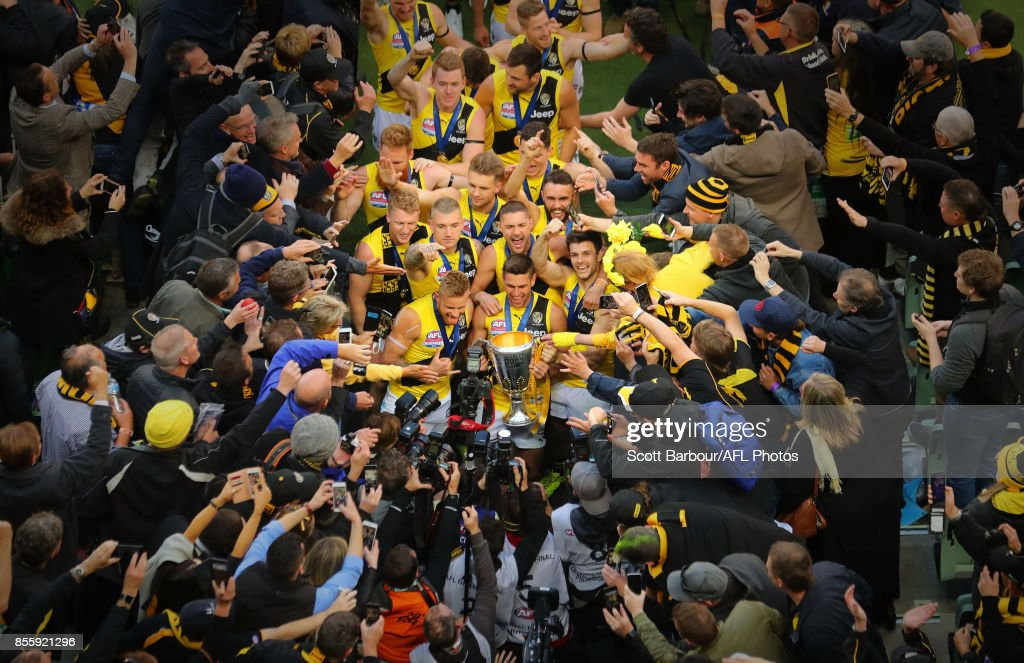 Trent Cotchin of the Tigers, Dustin Martin of the Tigers celebrate with the the AFL Premiership Cup and supporters in the crowd as the Tigers make their way to the changing rooms after winning the 2017 Toyota AFL Grand Final match between the Adelaide Crows and the Richmond Tigers at the Melbourne Cricket Ground on September 30, 2017 in Melbourne, Australia.
