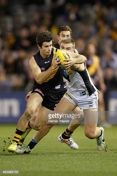 Trent Cotchin of the Tigers evades Ollie Wines of the Power during the round 17 AFL match between the Richmond Tigers and the Port Adelaide Power at...