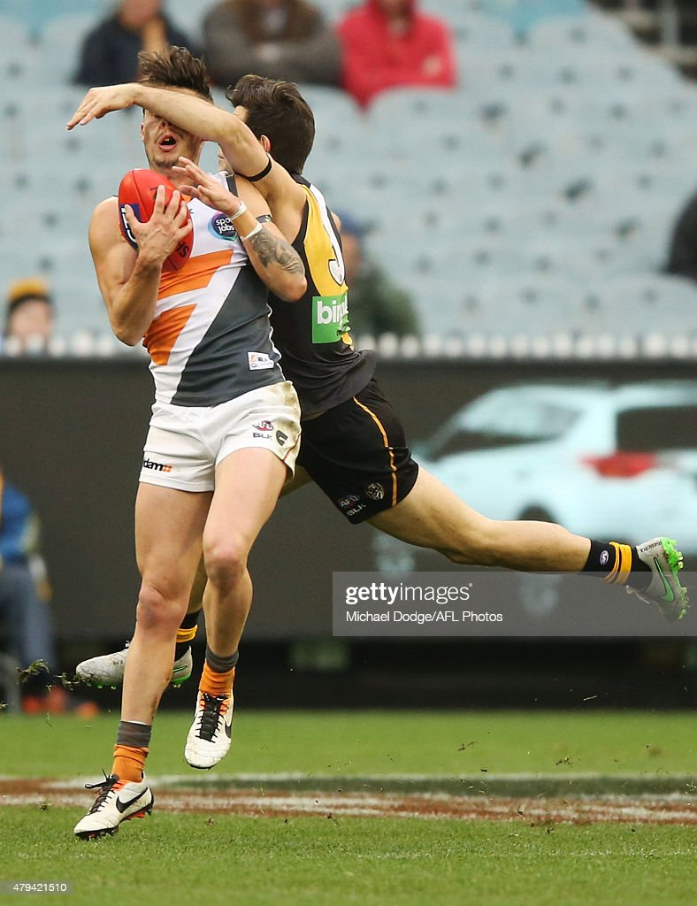 Trent Cotchin of the Tigers hits Zac Williams of the Giants with a forearm to the head during the round 14 AFL match between the Richmond Tigers and...