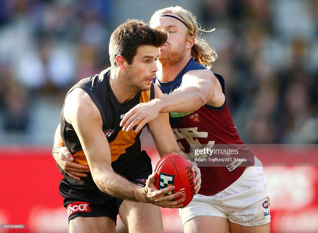 Trent Cotchin of the Tigers is tackled by Daniel Rich of the Lions during the 2016 AFL Round 14 match between the Richmond Tigers and the Brisbane Lions at the Melbourne Cricket Ground on June 25, 2016 in Melbourne, Australia.