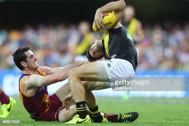 Trent Cotchin of the Tigers is tackled by Darcy Gardiner of the Lions during the round four AFL match between the Brisbane Lions and the Richmond...