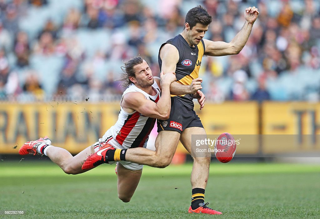 Trent Cotchin of the Tigers is tackled by Maverick Weller of the Saints as he kicks the ball during the round 22 AFL match between the Richmond...