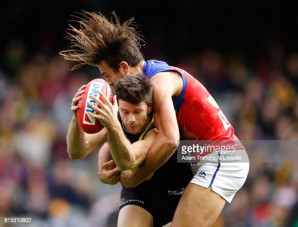 Trent Cotchin of the Tigers is tackled by Rhys Mathieson of the Lions during the 2017 AFL round 17 match between the Richmond Tigers and the Brisbane...