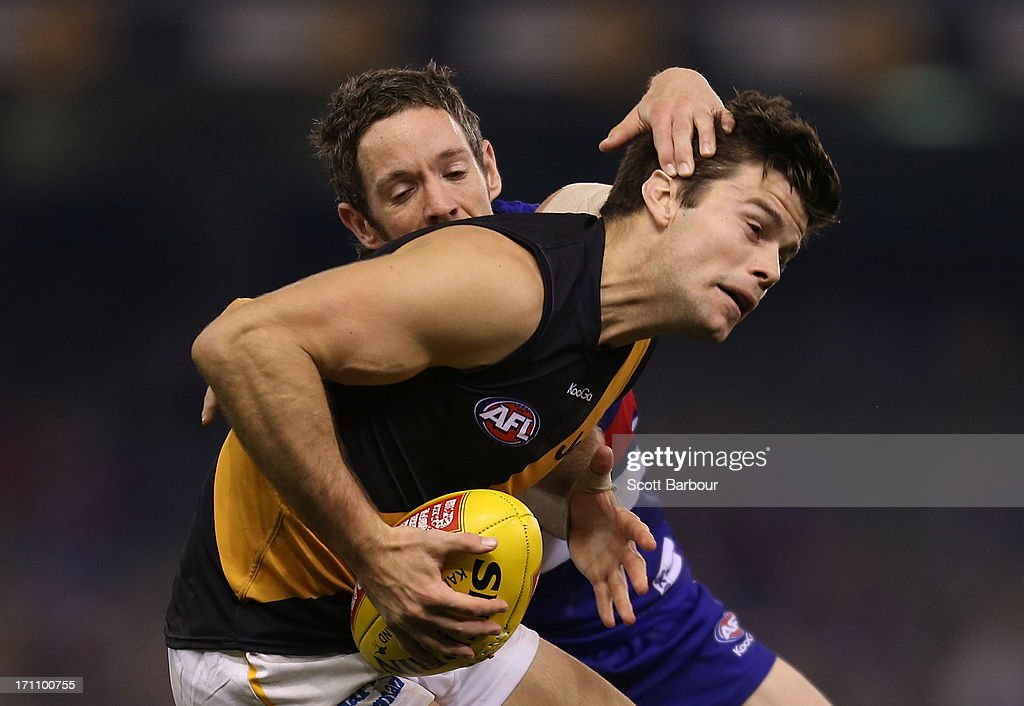 Trent Cotchin of the Tigers is tackled by Robert Murphy of the Bulldogs during the round 13 AFL match between the Western Bulldogs and the Richmond Tigers at Etihad Stadium on June 22, 2013 in Melbourne, Australia.