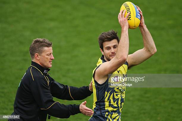 Trent Cotchin of the Tigers marks the ball next to Tigers head coach Damien Hardwick during a Richmond Tigers AFL training session at the ME Centre...