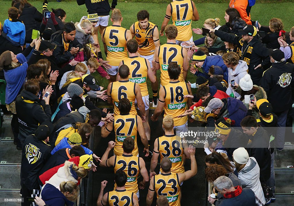 Trent Cotchin of the Tigers motivates teammates as they walk to their banner during the round 10 AFL match between the Essendon Bombers and the Richmond Tigers at Melbourne Cricket Ground on May 28, 2016 in Melbourne, Australia.