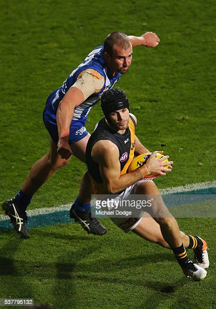 Trent Cotchin of the Tigers runs with the ball away from Ben Cunnington of the Kangaroos during the round 11 AFL match between the North Melbourne...