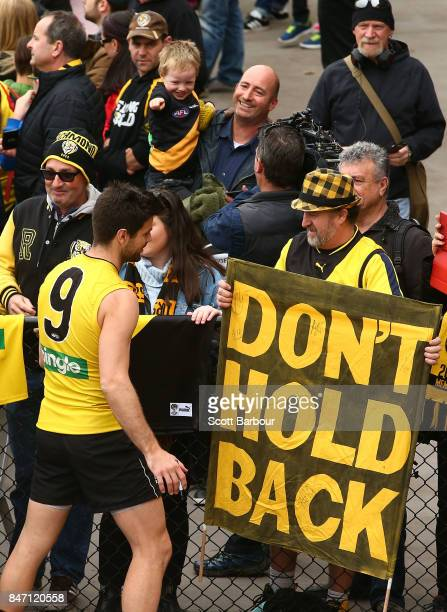 Trent Cotchin of the Tigers signs autographs for supporters in the crowd after a Richmond Tigers AFL training session at Punt Road Oval on September...