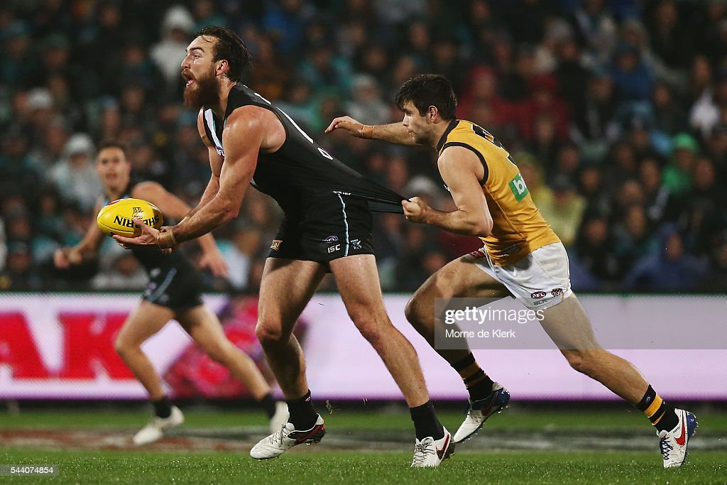 Trent Cotchin of the Tigers tackles Charlie Dixon of the Power during the round 15 AFL match between the Port Adelaide Power and the Richmond Tigers at Adelaide Oval on July 1, 2016 in Adelaide, Australia.