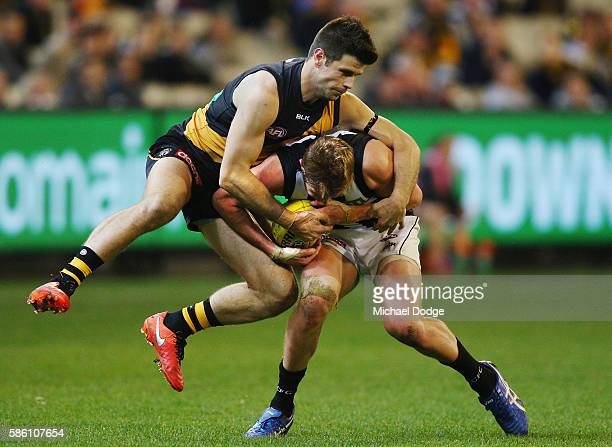 Trent Cotchin of the Tigers tackles Rupert Wills of the Magpies during the round 20 AFL match between the Richmond Tigers and the Collingwood Magpies...