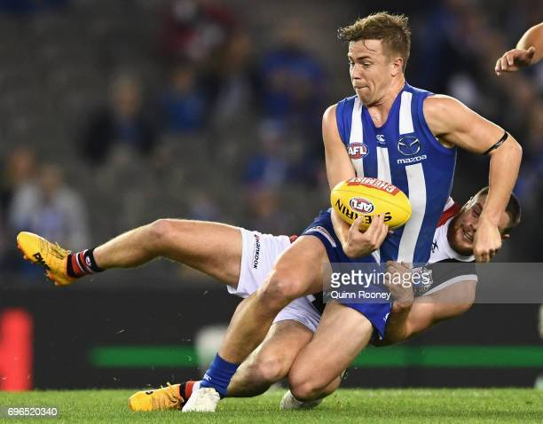 Trent Dumont of the Kangaroos handballs whilst being tackled by Jack Steven of the Saints during the round 13 AFL match between the North Melbourne...