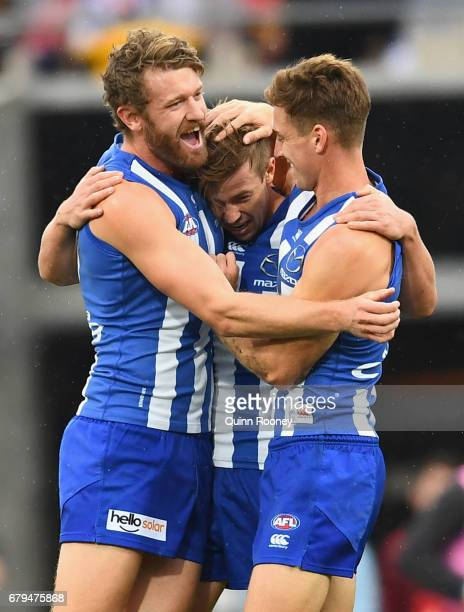 Trent Dumont of the Kangaroos is congratulated by team mates after kicking a goal during the round seven AFL match between the North Melbourne...