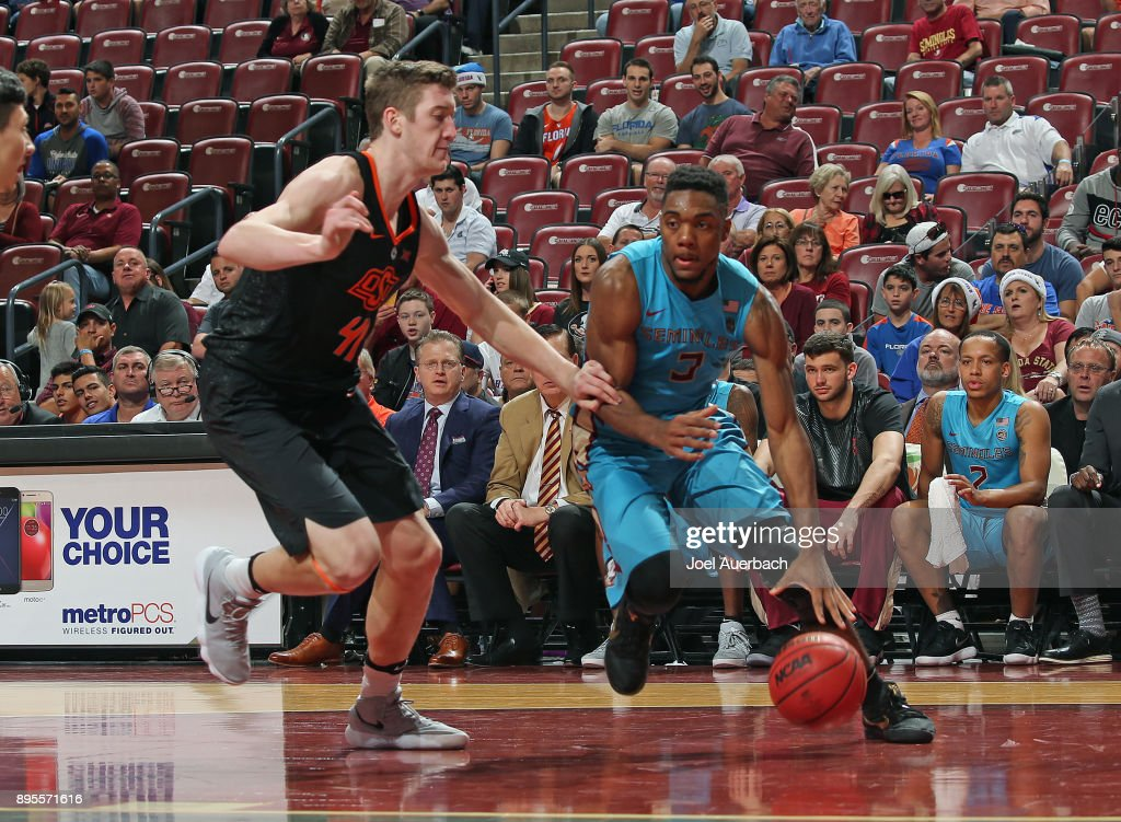 Trent Forrest #3 of the Florida State Seminoles drives to the basket against Mitchell Solomon #41 of the Oklahoma State Cowboys during the MetroPCS Orange Bowl Basketball Classic on December 16, 2017 at the BB&T Center in Sunrise, Florida. Oklahoma State defeated Florida State 71-70.