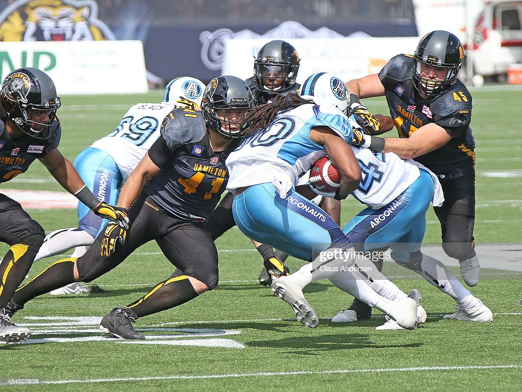 Trent Guy of the Toronto Argonauts is about to be tackled by Erik Harris of the Hamilton Tigercats in a CFL football game at Tim Hortons Field on...