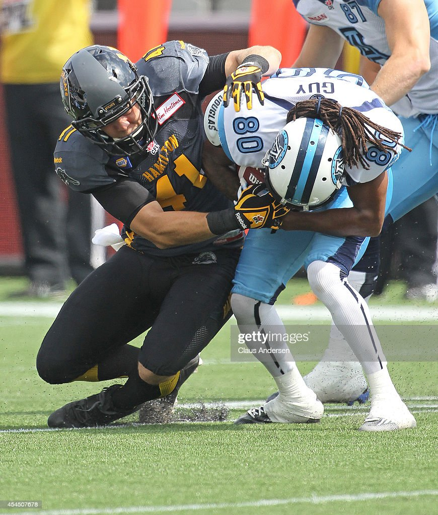 Trent Guy of the Toronto Argonauts is brought down by Erik Harris of the Hamilton Tigercats in a CFL football game at Tim Hortons Field on September...
