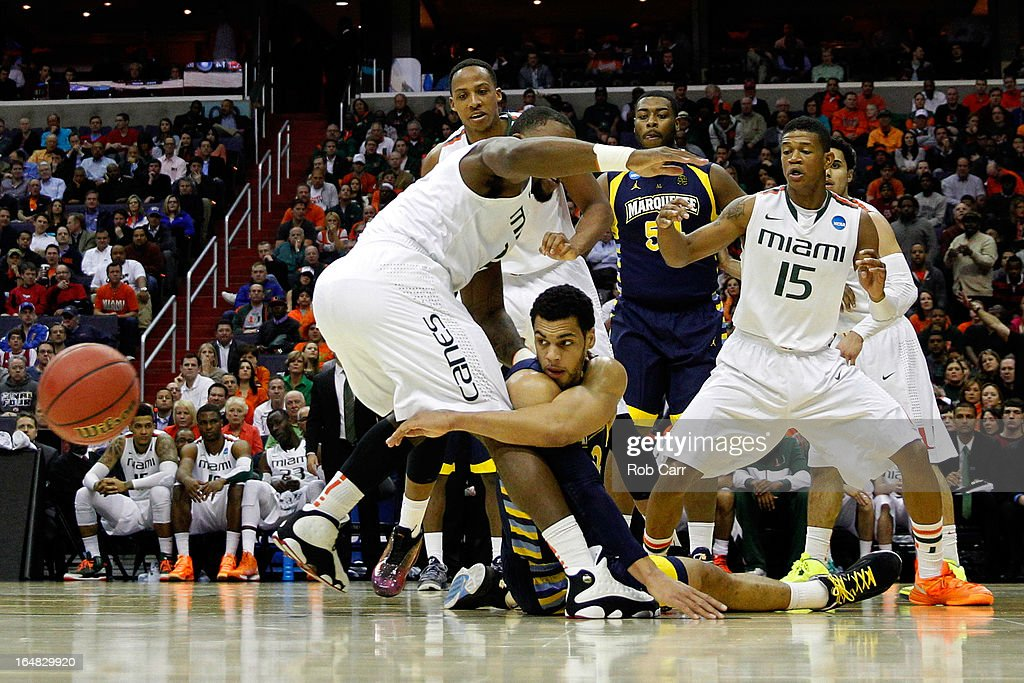 Trent Lockett #22 of the Marquette Golden Eagles passes the ball from the ground against Erik Swoope #21, Kenny Kadji #35 and Rion Brown #15 of the Miami (Fl) Hurricanes during the East Regional Round of the 2013 NCAA Men's Basketball Tournament at Verizon Center on March 28, 2013 in Washington, DC.