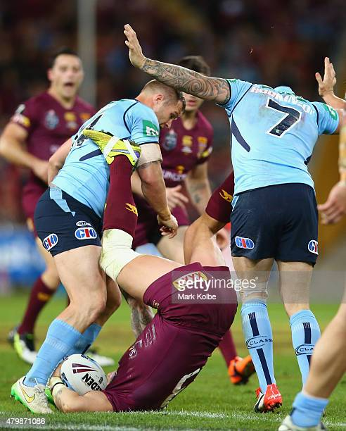 Trent Merrin and Trent Hodkinson of the Blues tackle Corey Parker of the Maroons in a dangerous tackle during game three of the State of Origin...
