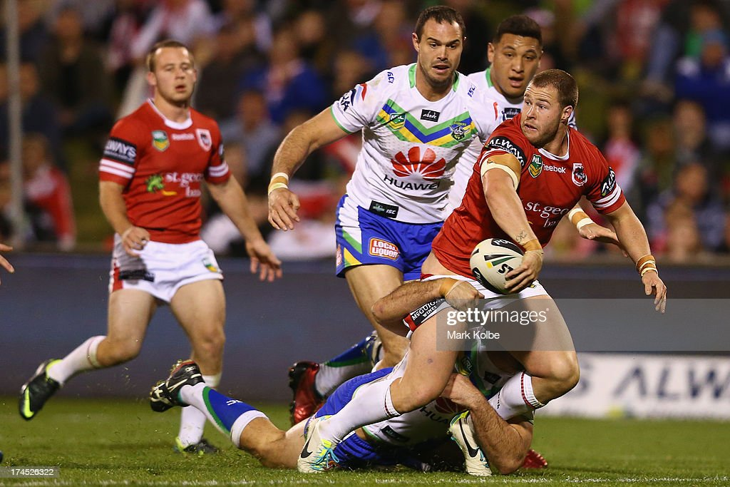 <a gi-track='captionPersonalityLinkClicked' href=/galleries/search?phrase=Trent+Merrin&family=editorial&specificpeople=5881493 ng-click='$event.stopPropagation()'>Trent Merrin</a> of the Dragons gets a pass away as he tackled during the round 20 match between the St George Illawarra Dragons and the Canberra Raiders at WIN Stadium on July 27, 2013 in Wollongong, Australia.