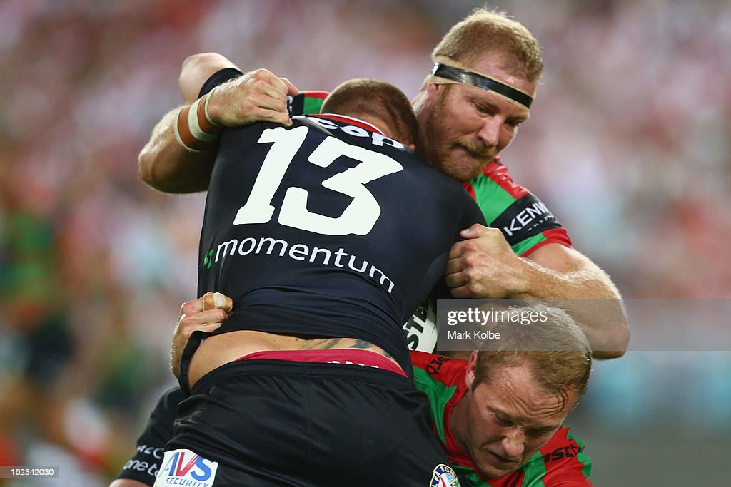Trent Merrin of the Dragons is tackled by Michael Croker of the Rabbitohs during the NRL Charity Shield match between the South Sydney Rabbitohs and the St George Illawarra Dragons at ANZ Stadium on February 22, 2013 in Sydney, Australia.
