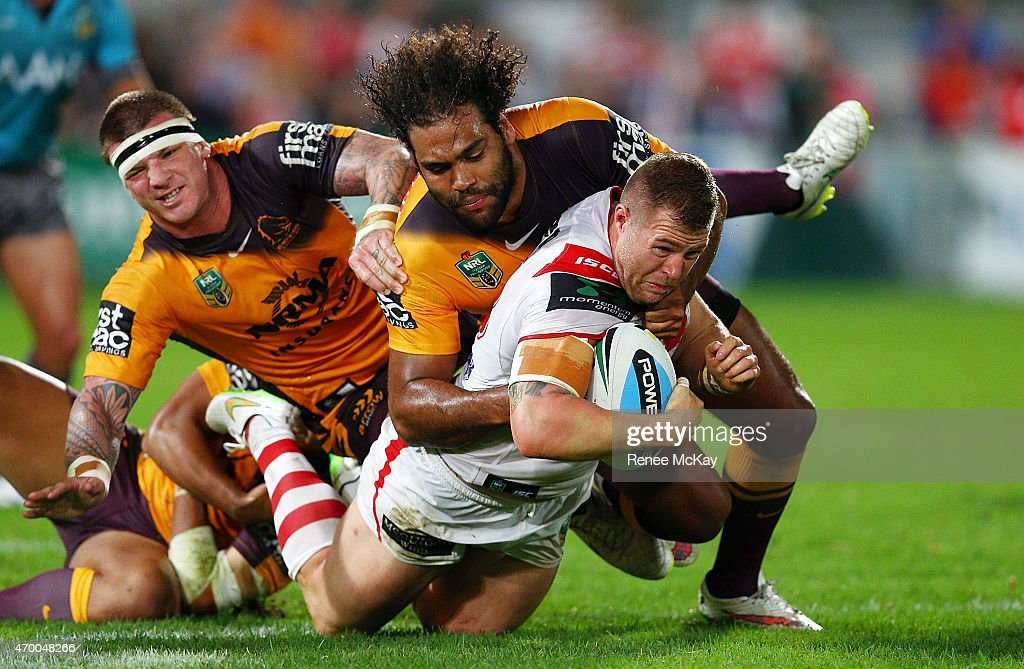 Trent Merrin of the Dragons is tackled by Sam Thaiday and Josh McGuire of the Broncos during the round seven NRL match between the St George...