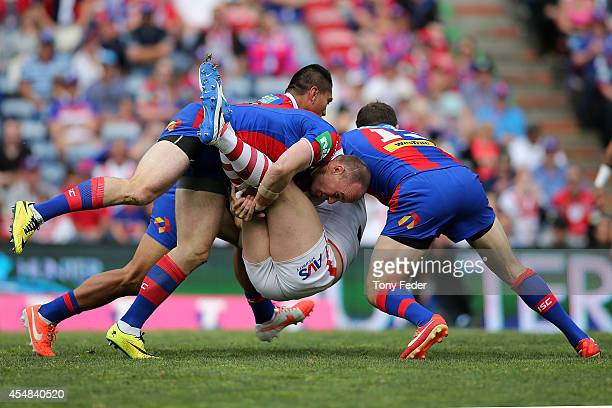 Trent Merrin of the Dragons is tackled by the Knights defence during the round 26 NRL match between the Newcastle Knights and the St George Illawarra...