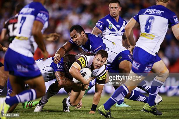 Trent Merrin of the Panthers is tackled during the round two NRL match between the Penrith Panthers and the Canterbury Bulldogs at Pepper Stadium on...