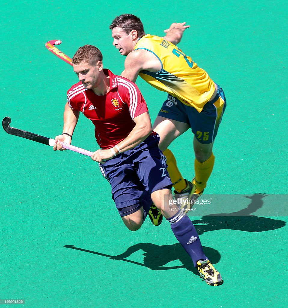 Trent Mitton of Australia (R) challenges Richard Smith of England (L) during their match on the final day at the International Super Series hockey tournament in Perth on November 25, 2012. AFP PHOTO / Tony ASHBY IMAGE