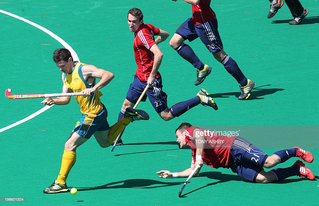 Trent Mitton of Australia (L) runs past Simon Egerton (R) and David Condon (C) of England during their match on the final day of the International Super Series hockey tournament in Perth on November 25, 2012. AFP PHOTO / Tony ASHBY IMAGE