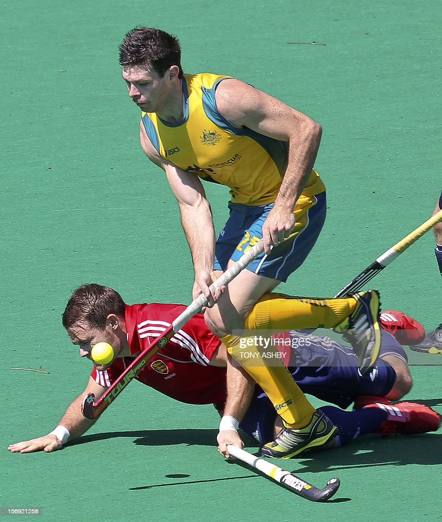 Trent Mitton of Australia (front) runs past Simon Egerton of England during their match on the final day of the International Super Series hockey tournament in Perth on November 25, 2012. AFP PHOTO / Tony ASHBY IMAGE