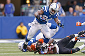 Trent Richardson of the Indianapolis Colts breaks a tackle by Jayson DiManche of the Cincinnati Bengals during the first quarter on October 19 2014...
