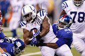 Trent Richardson of the Indianapolis Colts gets tackled by Walter Thurmond III of the New York Giants in the first half of an NFL preseason game at...