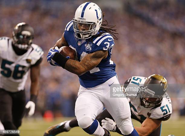 Trent Richardson of the Indianapolis Colts runs for a fist quarter touchdown through the tackle of Paul Posluszny of the Jacksonville Jaguars at...