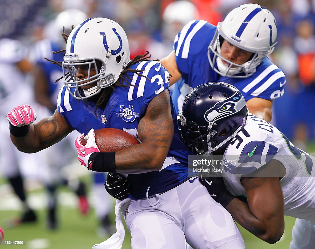 Trent Richardson #34 of the Indianapolis Colts runs the ball as Chris Clemons #91 of the Seattle Seahawks wraps him up for a tackle from behind at Lucas Oil Stadium on October 6, 2013 in Indianapolis, Indiana.