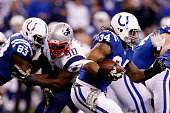 Trent Richardson of the Indianapolis Colts runs the ball as teammate Dwayne Allen blocks Zach Moore of the New England Patriots during the first...